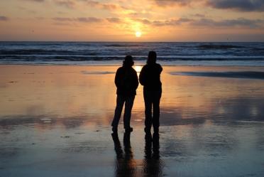 Two friends in silouhette gaze at orange sunset over Benson Beach